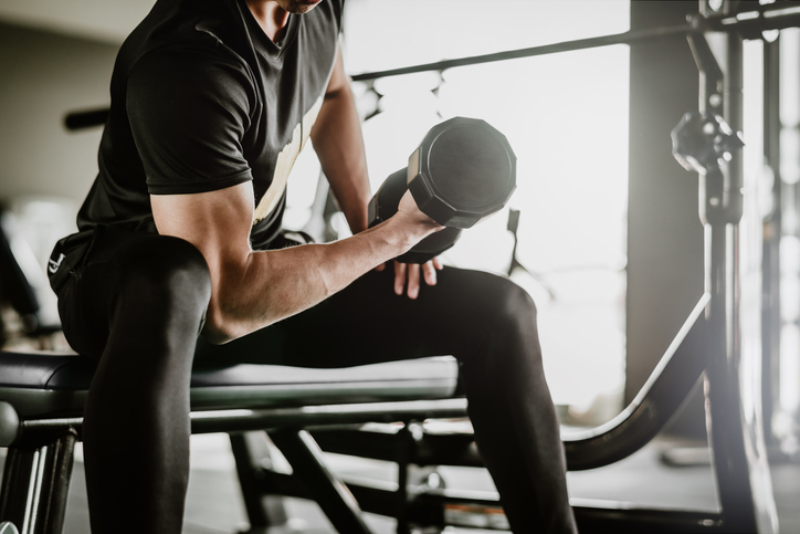 ジムで腕のトレーニングをする男性